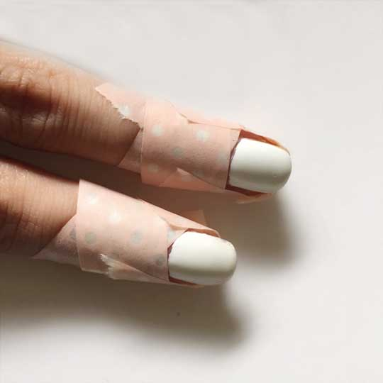"""I made a little """"x"""" at the base of the cuticle first. Then I placed some tape over the tip of my finger and wrapped it around the sides."""