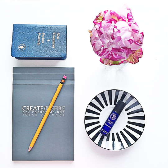 Constants by my bedside table! A line-free notebook, my mini Bible, essential oils to relax, and a pretty flower.